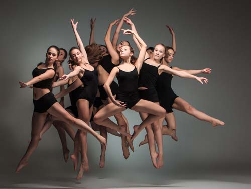The group of modern ballet dancers jumping on gray background