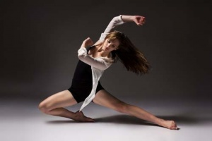 Beautiful slim young female modern jazz contemporary style ballet dancer wearing a black leotard and white shirt on a neutral grey studio background