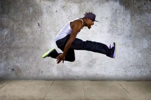hip hop dancer jumping high on a concrete background
