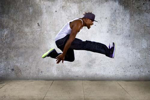hip hop dancer jumping high on a concrete background
